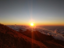 Sun setting in a sea of clouds seen from Mount Rinjani Indonesia