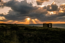 Sun Spears over the remains of a tin mine in Cornwall England