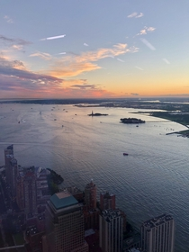 Sunset from the top floor of One World Trade Center overlooking the Statue of Liberty and NY harbor