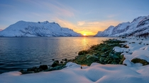 Sunset in the ocean between the mountains out in the fjord Ersfjordbotn Troms Fylke Norway  by John A Hemmingsen