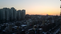 Sunset over the snow covered rooftops of Ahyeon neighborhood Mapo District Seoul South Korea