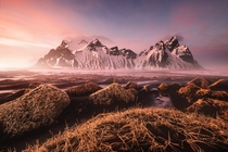 Sunset splashes a rosy tint over the landscape The mountain is the -foot -meter Vestrahorn a main landmark of southeastern Iceland  by Fabrizio Fortuna
