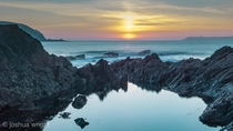 Sunset through a welsh rock pool Pembrokeshire coast national park Wales