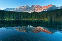Sunshine in a mirror Carezza Lake in the Italian Dolomites Photo by Simone Panzeri