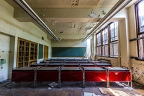 Symmetrical red desks in an abandoned Detroit school Unfortunately the school was burned to the ground accidentally by scrapping thieves that week