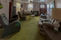 Tacky carpet and old furniture in an almost fully intact living room in an abandoned house in Ontario Canada OC -
