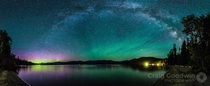 The Aurora Borealis dances in the lower left corner green waves of Airglow hover to the right and the Milky Way arch rises over it all Priest Lake Idaho United States