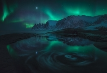 The Aurora reflecting in a swirling tide pool Senja Norway