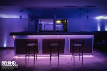 The bar of an abandoned nightclub illuminated by blue lights that still work