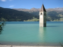 The Bell Tower of the old town of Curon now under water of the dam of the reservoir of Lake Resia Italy