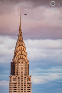 The Chrysler Building in NYC at sunset as a plane flies past