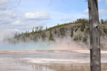 The colors from Grand Prismatic in Yellowstone reflect into the steam rising from it