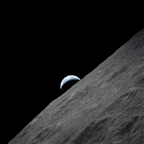 The crescent Earth rises above the Moons horizon in this photograph taken from the Apollo  spacecraft in lunar orbit during its final lunar landing mission in the Apollo program