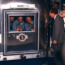 The crew of Apollo  being addressed by President Nixon as they wait in quarantine after returning from their historic mission to the Moon  July