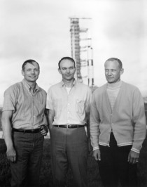 The crew of Apollo  poses in front of their Saturn V