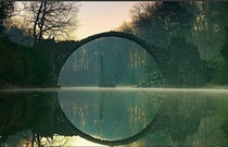 The Devils bridge is a th century structure in Kromlau Germany that was designed to make a perfect circle with its reflection in the water below