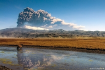 The eruption of Eyjafjallajkull seen over a beautiful Icelandic landscape  photo by Frijfur M