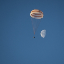 The Expedition  Soyuz parachuting down to Earth with the Moon in the background