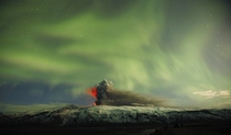 The Eyjafjallajokull volcano erupts in  with a stunning display of the Northern Lights in the background Iceland -