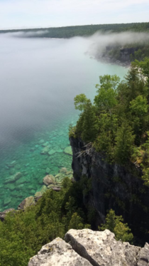 The fog moves off the escarpment revealing the turquoise water and white rocks below A reminder that Ontario is beautiful too Bruce Peninsula National Park