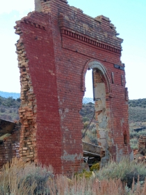 The front of a ruined bank in a ghost town in central Nevada
