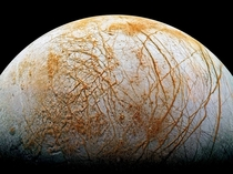 The frozen fissured surface of Jupiters moon Europa seen here in a colorized mosaic image from the Galileo spacecraft