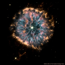 The Glowing Eye Planetary nebula NGC  is roughly x as wide as our solar system and the hot stellar core within is estimated to have a surface temperature of about  degrees Celsius
