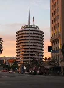 The iconic Capitol Records Building at sunset viewed from the corner of Hollywood amp Vine Completed in  its an excellent example of the futuristic Googie style of architecture
