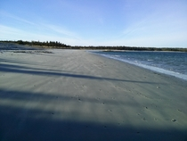 The long shadows of winter creep their way across a deserted Taylor Head Beach Nova Scotia