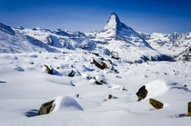 The Matterhorn standing tall over a snowy field of boulders - above Zermatt Switzerland