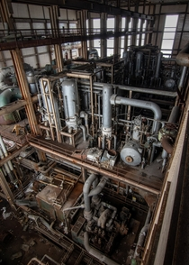 The maze of pipes inside a large abandoned power plant