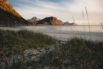 The midnight sun coloring the mountains and white sands of Haukland Beach in Norways Lofoten Islands