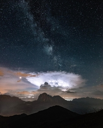 The milky way and a storm cloud erupting over the mountains of Northern Italy