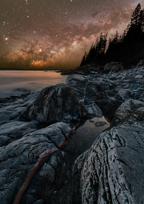 The Milky Way rises over copper leading lines on the shore of Acadia National Park