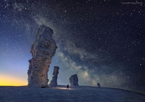 The Milky Way seen over the Manpupuner or Seven Strong Men rock formations in northern Russia photographed in February  by Sergei Makurin