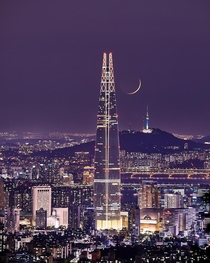 The moon between two towers in Seoul Korea