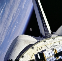 The moon is framed between the Space Shuttle orbiters OMS Orbital Maneuvering System pod and the Earth limb over the Atlantic Ocean as seen from the aft windows onboard Discovery on mission STS-