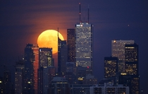 The moon rises behind the skyline and financial district in Toronto on November   Mark Blinch