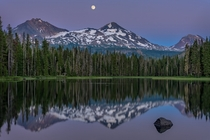 The moon rises over the Three Sisters Mountains at Scott Lake Oregon  by Kevin Brown