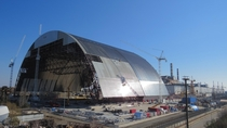 The New Safe Confinement arch here under construction but now straddling the bursten Chernobyl nuclear reactor
