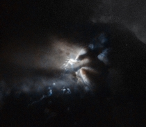The newborn star RNO  is hidden in this image revealed only by light reflected onto the plumes of the dark cloud