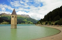 The partly submerged church bell tower of Lake Reschen South Tyrol Italy