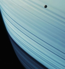 The rings are nearly edge-on in this equatorial view of Saturn and two of its moons -- Mimas and Tethys Cassini captured this image on July