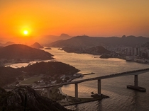 The setting sun sinks behind the low mountains framing Vila Velha a coastal city in the Brazilian state of Esprito Santo Victor Lima