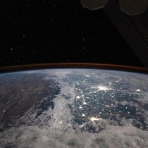 The snow-covered Himalayan Mountains and the bright city lights of New Delhi India and Lahore Pakistan are also visible below the faint orange airglow of atmospheric particles reacting to solar radiation taken from the International Space Station