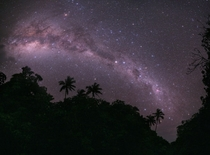 The southern Milky Way viewed over the hilltops lined with palm trees just outside a village in Turkey