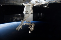 The SpaceX Dragon and the Canadarm with Earths horizon in the background