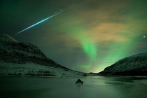 The sudden flash of a fireball meteor from the  Geminid meteor shower streaks across an Aurora Borealis-filled night sky near Troms Norway  by Bjrnar G Hansen