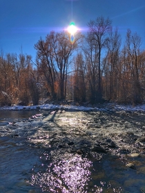 The sun casting purple rays over the Roaring Fork River in Basalt CO x