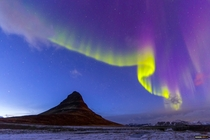 The sun hadnt set fully yet they were so bright they were dancing over this triangular mountain Kirkjufell Iceland